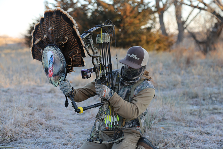 turkey hunter mounting Heads Up decoy to bow