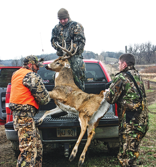 hunters loading buck in truck