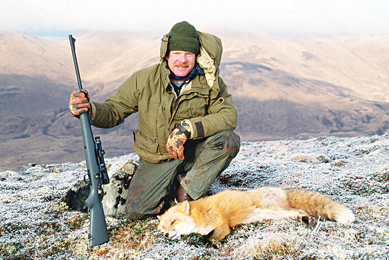 Craig Boddington with red fox and rifle on mountain