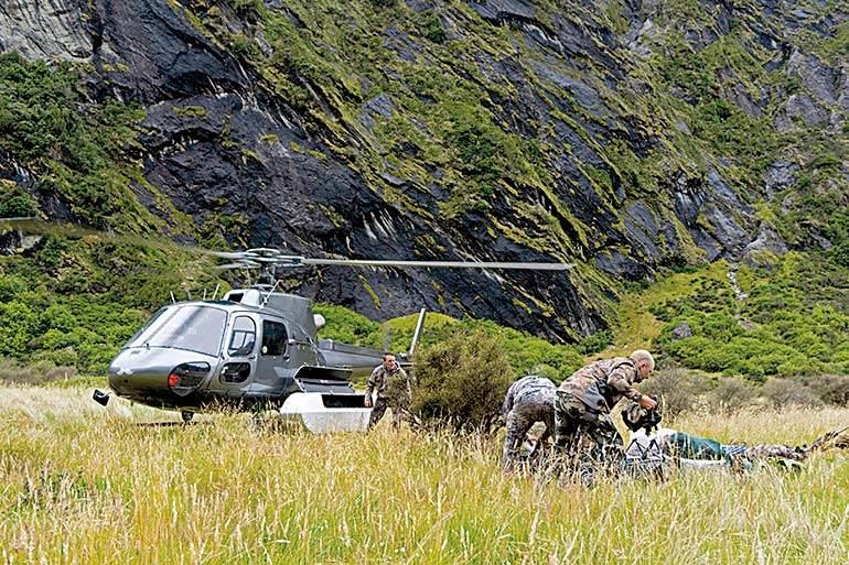 hunters exiting helipopter inNew Zealand backcountry