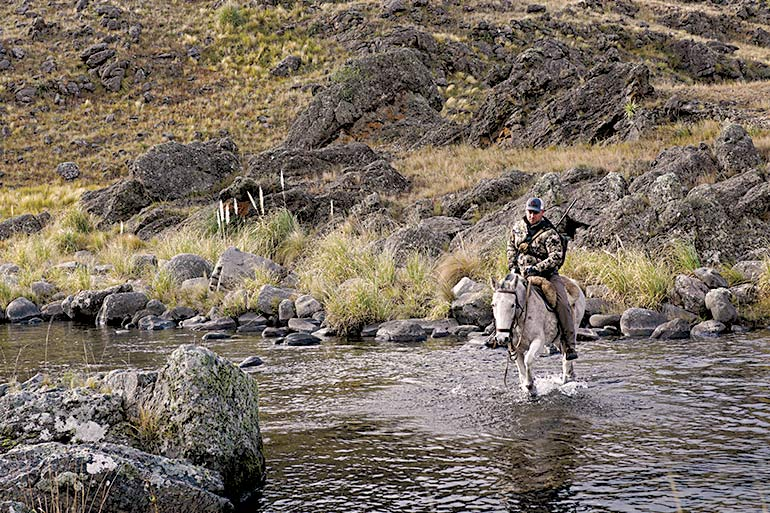 hunter riding horse across water in Argentina