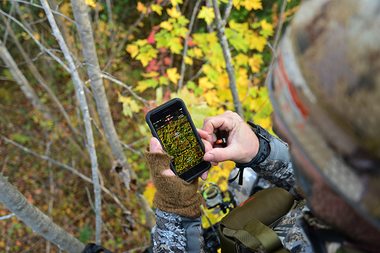 bowhunter using onX from treestand