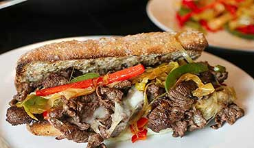 A satisfying recipe for venison cheesesteak sandwiches with sautéed leeks, bell peppers and hot provolone cheese.