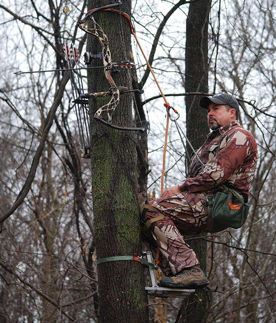 bowhunter sitting in tree saddle