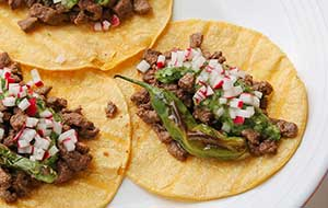 Shishito peppers are delightful in this venison recipe, and with the subtle spiciness from crispy diced radish coupled with an herbaceous, tangy green sauce, these tacos are perfect bites.