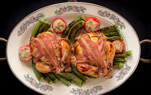For an elegant dinner for two, roast individual poussin in bacon until golden brown and serve with oven-roasted okra and stuffed cherry peppers.