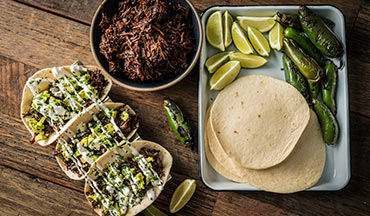 To make this recipe, braise wild game neck, shoulder, or arm meat, then add Traeger's Sriracha Sugar Lips Sauce and serve in warm flour tortillas straight from the grill.