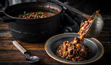 Get ready to braise ground venison with all the traditional chili ingredients, directly on the grill, for a smokin' hot take on this comfort food classic.