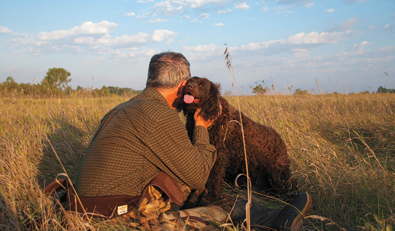 Hunter hugging American Water Spaniel