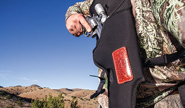 The DeSantis custom holster for a scoped revolver is a comfortably worn solution to carrying a heavy handgun in the field. The ballistic nylon material and pack-cloth lining is resilient and quick to draw from.