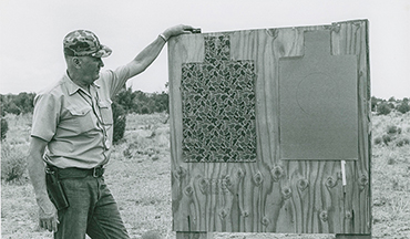 Originally designed by Cooper from his earlier API target of the late 1970s, the current Gunsite Option Target is a square border humanoid measuring 18 inches by 30 inches, overlaying three different shades of tan and brown in a camouflage pattern to subdue the borders and mute the scoring zones.