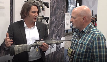 As OSG's Lynn Burkhead looks on, Jared Hinton of Savage Arms shows off a wall full of new rifle options in the new Mossy Oak Overwatch camo pattern.