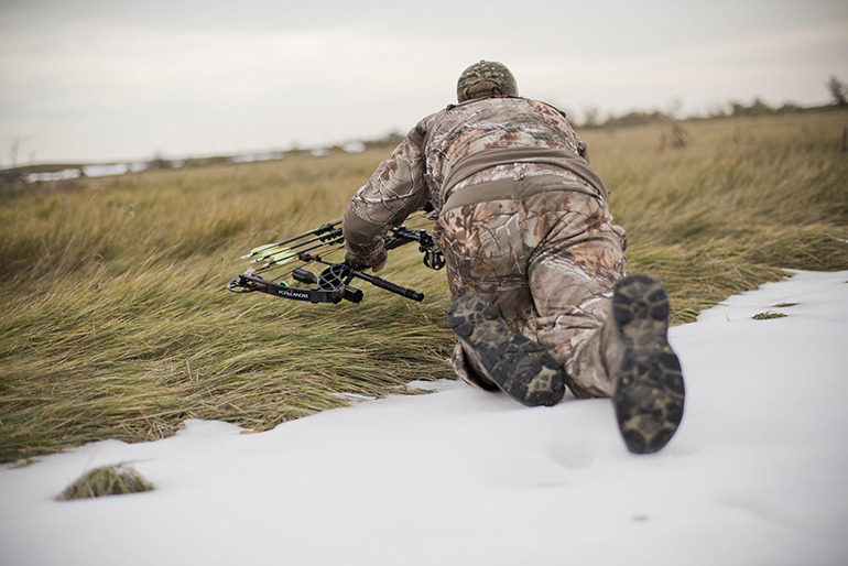 bowhunter stalking through snowy field