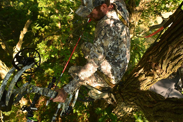 bowhunter at full draw in treestand