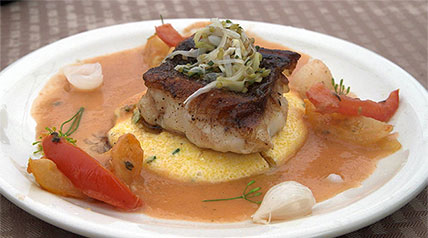 With creamy polenta, slow-roasted tomatoes and cipollini onions with smoky fennel sauce.