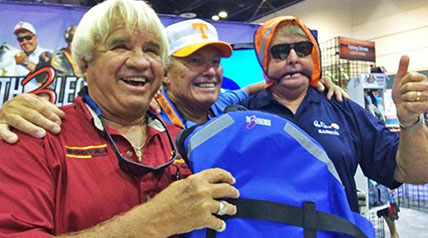 Bill Dance draped a life jacket over his head, a strap like a bridle in his mouth, as he stood alongside Roland Martin and Jimmy Houston for a photo op on the ICAST floor.