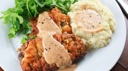 This paleo friendly chicken-fried venison steak recipe is made with coconut flour, and tastes amazing covered in gravy with a side of mashed cauliflower.