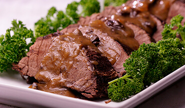 In this recipe, a bear roast is prepared Sauerbraten style. The meat is marinated in a mixture of red wine, vinegar, and spices, and then braised and served with a hearty gravy.