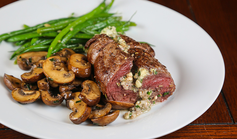 Filled with blue cheese and herbs such as shallot, garlic, chives and rosemary, this stuffed elk venison tenderloin recipe will make your house smell wonderful