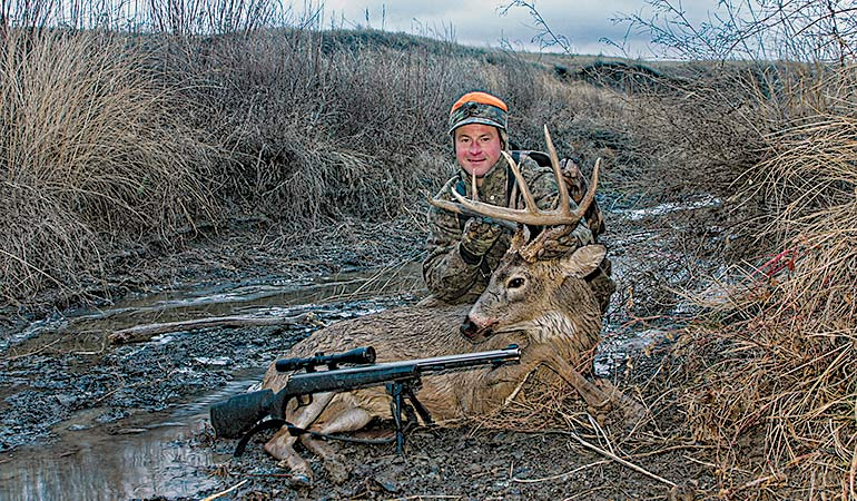 Mark Kayser with mature whitetail buck in freezing rain