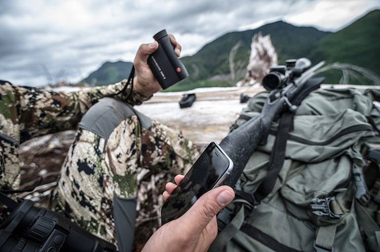 rifle hunter holding phone and Leica rangefinder