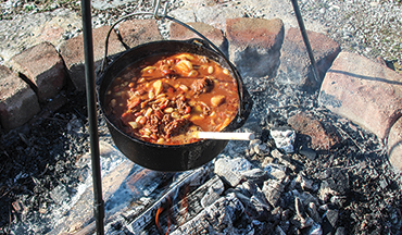 A Dutch oven over an open fire is the perfect way to cook this hearty bean dish.