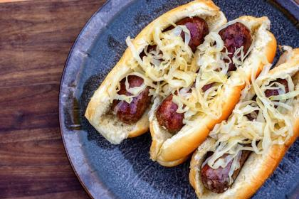 These juicy, flavorful venison brats are cooked and served up Wisconsin-style – simmered in beer, finished on the grill, and served with hard-cider sauerkraut and quality mustard.