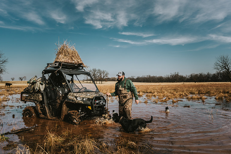 Duck hunter and dog in water with ATV
