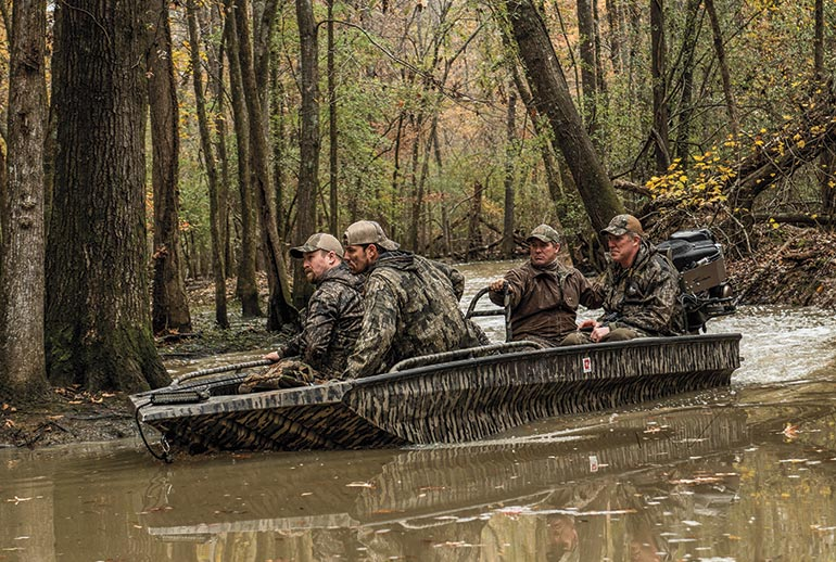 Duck hunters in boat in timber
