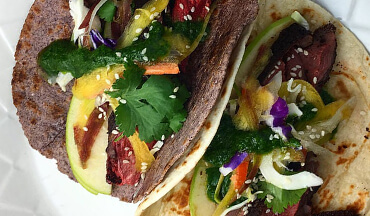 Serve smoked goose in warm tortillas with slices of tart green apple, crispy cabbage, shaved carrots, and a small amount of cilantro sauce.