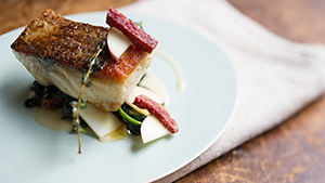 This is a fresh, citrus take on surf and turf with a mix of wild striped bass and fried salami.