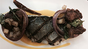 A grilled European seabass with some Mediterranean flair.