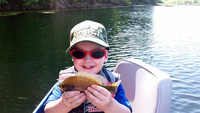 A young angler is delighted to hold up a bluegill.